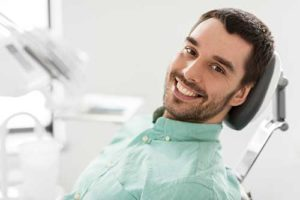 man smiling in dentist chair getting periodontics heights tx